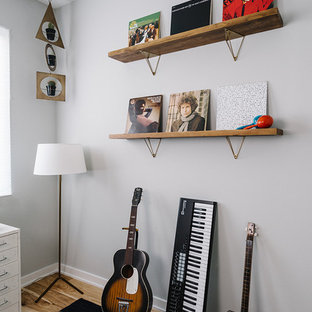 Inspiration for a mid-sized scandinavian freestanding desk medium tone wood floor home studio remodel in Austin with gray walls