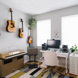Cette image montre un bureau nordique de taille moyenne et de type studio avec un mur gris, un sol en bois brun, aucune cheminée et un bureau indépendant.