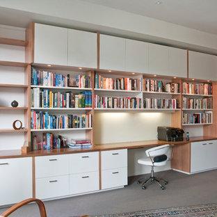 Modern inredning av ett stort hemmabibliotek, med vita väggar, heltäckningsmatta och ett inbyggt skrivbord