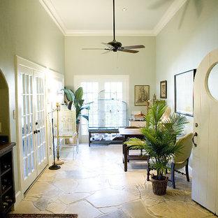 Imagen de despacho bohemio, de tamaño medio, con paredes verdes, suelo de piedra caliza, escritorio independiente y suelo beige