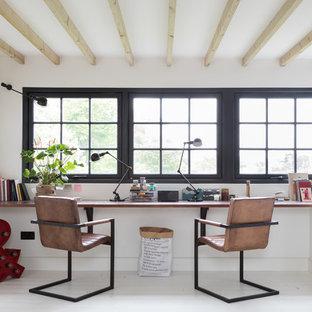 Foto på ett industriellt arbetsrum, med vita väggar, målat trägolv, ett inbyggt skrivbord och vitt golv