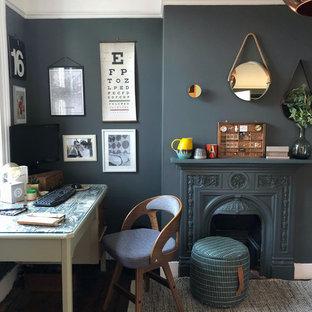 ロンドンの中くらいのトランジショナルスタイルのおしゃれな書斎 (グレーの壁、濃色無垢フローリング、標準型暖炉、金属の暖炉まわり、自立型机、茶色い床) の写真