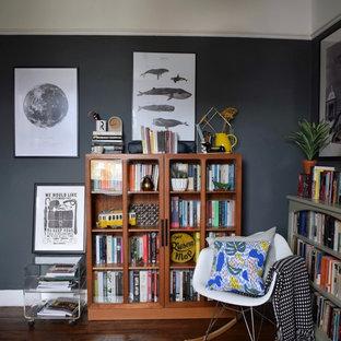 ロンドンの中サイズのトランジショナルスタイルのおしゃれな書斎 (グレーの壁、濃色無垢フローリング、標準型暖炉、金属の暖炉まわり、自立型机、茶色い床) の写真