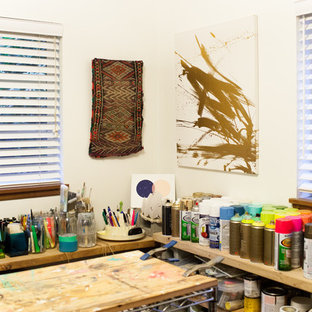 Cette photo montre un petit bureau sud-ouest américain de type studio avec un mur blanc, un sol en bois brun et un bureau indépendant.