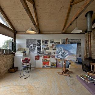 Esempio di un atelier rustico con pareti bianche e stufa a legna