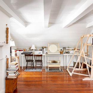 Diseño de estudio de estilo de casa de campo con paredes blancas, suelo de madera oscura, chimenea tradicional, escritorio empotrado y suelo marrón