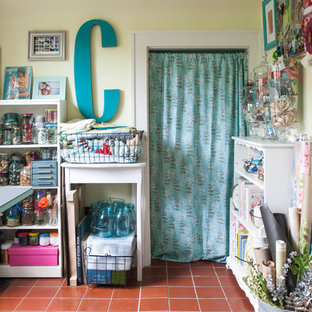 Craft room - small eclectic freestanding desk terra-cotta floor craft room idea in Columbus with yellow walls and no fireplace
