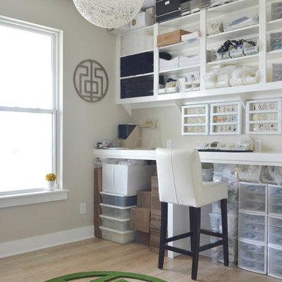 Craft room - contemporary built-in desk light wood floor craft room idea in Dallas with gray walls