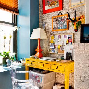 Inspiration för eklektiska hemmabibliotek, med mellanmörkt trägolv och ett fristående skrivbord