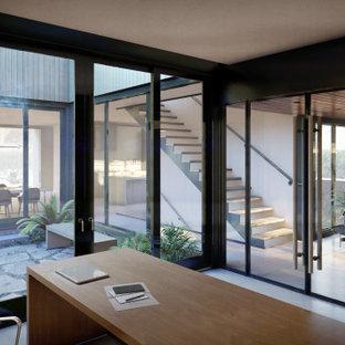 Cette image montre un bureau minimaliste avec un sol en carrelage de porcelaine, un sol gris, un bureau indépendant et un mur en parement de brique.