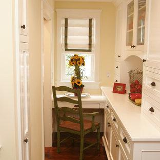 Foto di un piccolo studio stile marinaro con pareti gialle, parquet scuro e scrivania incassata