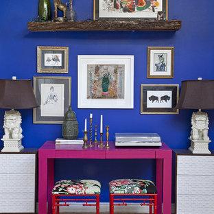 Idee per uno studio eclettico con pareti blu, pavimento in legno massello medio e scrivania autoportante