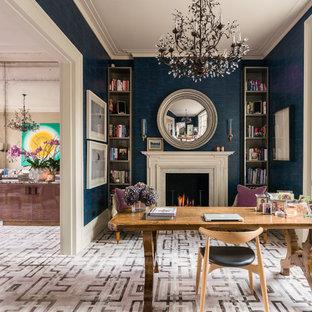 Foto på ett mellanstort vintage hemmabibliotek, med blå väggar, heltäckningsmatta, en spiselkrans i gips, ett fristående skrivbord och en standard öppen spis