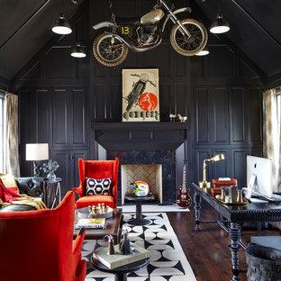Foto på ett stort funkis hemmabibliotek, med svarta väggar, mörkt trägolv, en standard öppen spis, ett fristående skrivbord och brunt golv