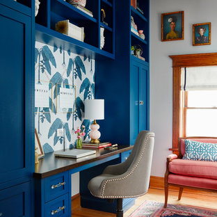 Study room - transitional built-in desk medium tone wood floor study room idea in Chicago with white walls