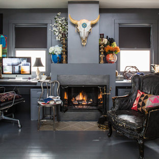Example of a mid-sized eclectic built-in desk painted wood floor study room design in Los Angeles with gray walls, a standard fireplace and a plaster fireplace