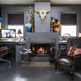 Пример оригинального дизайна: рабочее место среднего размера в стиле фьюжн с серыми стенами, деревянным полом, стандартным камином, встроенным рабочим столом и фасадом камина из штукатурки