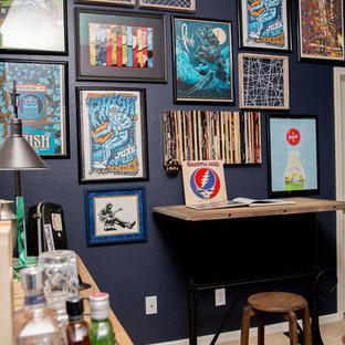 Foto på ett litet industriellt hemmabibliotek, med blå väggar, heltäckningsmatta, ett fristående skrivbord och beiget golv