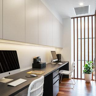 サンシャインコーストの中サイズのコンテンポラリースタイルのおしゃれな書斎 (白い壁、無垢フローリング、造り付け机、マルチカラーの床) の写真