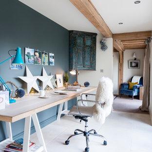 Ejemplo de despacho rústico con paredes azules y escritorio independiente