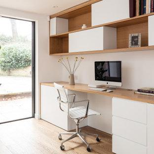 Идея дизайна: рабочее место среднего размера в скандинавском стиле с белыми стенами, светлым паркетным полом, встроенным рабочим столом и бежевым полом без камина