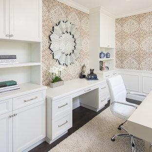 Mittelgroßes Klassisches Arbeitszimmer ohne Kamin mit Arbeitsplatz, rosa Wandfarbe, dunklem Holzboden, freistehendem Schreibtisch und braunem Boden in Los Angeles