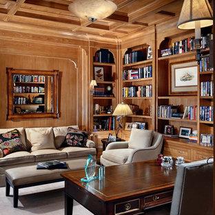 Modelo de despacho tradicional, de tamaño medio, con paredes beige, suelo de madera oscura, suelo marrón, escritorio independiente, chimenea tradicional y marco de chimenea de baldosas y/o azulejos