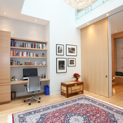 Example of a large trendy built-in desk light wood floor study room design in Toronto with white walls and no fireplace