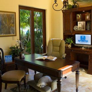 マイアミの広い地中海スタイルのおしゃれな書斎 (黄色い壁、トラバーチンの床、自立型机、ベージュの床) の写真