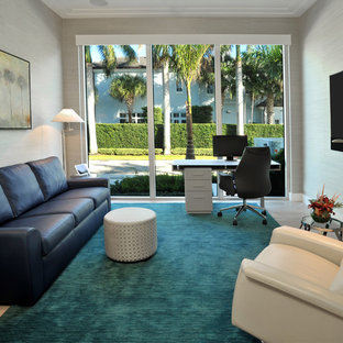This is an example of a classic study in Miami with grey walls, carpet, a freestanding desk and turquoise floors.