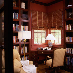 Exempel på ett litet lantligt hemmabibliotek, med röda väggar, mellanmörkt trägolv och ett inbyggt skrivbord
