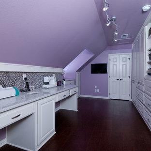 Imagen de sala de manualidades tradicional, de tamaño medio, sin chimenea, con paredes púrpuras, suelo de madera oscura, escritorio empotrado y suelo marrón