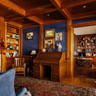 Inspiration pour un grand bureau craftsman avec un mur bleu, un sol en bois brun, une cheminée standard, un manteau de cheminée en pierre, un bureau indépendant et un sol marron.