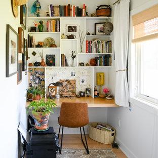 Foto på ett eklektiskt arbetsrum, med vita väggar, mellanmörkt trägolv, ett inbyggt skrivbord och brunt golv