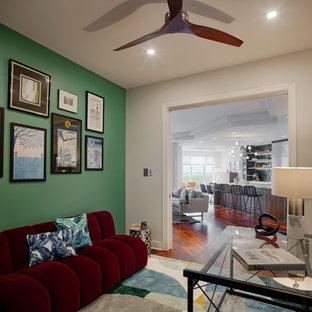 Immagine di un grande studio minimalista con libreria, pareti verdi, parquet scuro, nessun camino, scrivania autoportante e pavimento rosso