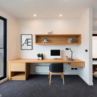 メルボルンのコンテンポラリースタイルのおしゃれなホームオフィス・仕事部屋 (白い壁、カーペット敷き、造り付け机、黒い床) の写真