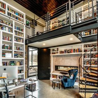 Immagine di un ampio studio moderno con libreria, pareti grigie, pavimento in cemento, camino bifacciale, cornice del camino in cemento e scrivania autoportante