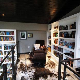 他の地域の広いモダンスタイルのおしゃれなホームオフィス・書斎 (ライブラリー、白い壁、コンクリートの床、両方向型暖炉、木材の暖炉まわり、自立型机) の写真
