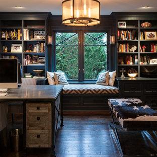 Industriell inredning av ett mellanstort hemmabibliotek, med mörkt trägolv, en standard öppen spis, en spiselkrans i tegelsten, ett fristående skrivbord och blå väggar