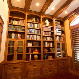 Foto på ett mellanstort vintage arbetsrum, med beige väggar, ett bibliotek, mörkt trägolv och brunt golv