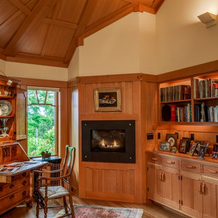 Medium sized traditional study in Portland Maine with beige walls, a metal fireplace surround, a freestanding desk, a standard fireplace, light hardwood flooring and beige floors.