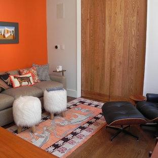 ニューヨークの小さいモダンスタイルのおしゃれなホームオフィス・書斎 (ライブラリー、オレンジの壁、無垢フローリング、暖炉なし、自立型机、茶色い床) の写真