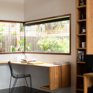 This is an example of a contemporary study room in Melbourne with white walls, dark hardwood floors, a built-in desk and brown floor.