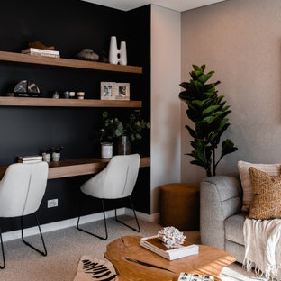 シドニーのコンテンポラリースタイルのおしゃれなホームオフィス・書斎 (黒い壁、カーペット敷き、造り付け机、グレーの床) の写真