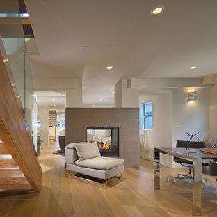 Ispirazione per un ufficio design di medie dimensioni con camino bifacciale, pareti bianche, parquet chiaro, cornice del camino piastrellata e scrivania autoportante