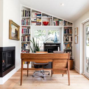 Стильный дизайн: кабинет среднего размера в современном стиле с белыми стенами, светлым паркетным полом, угловым камином, отдельно стоящим рабочим столом и бежевым полом - последний тренд