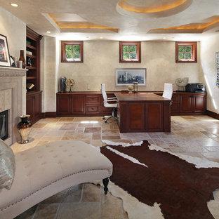Exempel på ett stort klassiskt hemmabibliotek, med beige väggar, kalkstensgolv, en standard öppen spis, en spiselkrans i trä, ett inbyggt skrivbord och beiget golv