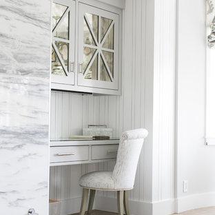 Modelo de despacho tradicional renovado con paredes grises, suelo de madera en tonos medios y escritorio empotrado