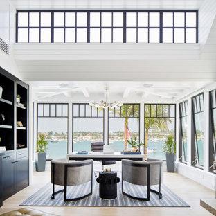 Cette photo montre un très grand bureau bord de mer avec un mur blanc, un sol en bois clair, un bureau indépendant et un sol beige.