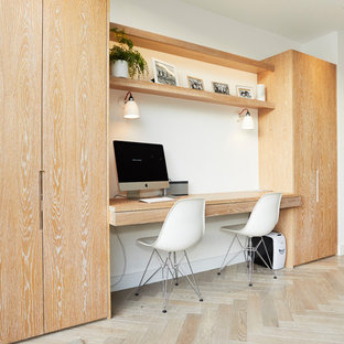 This is an example of a small contemporary home office and library in London with white walls, light hardwood flooring, a built-in desk and beige floors.